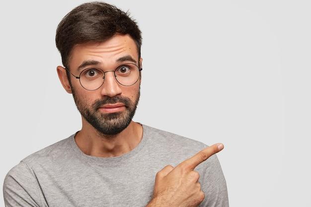 Foto de guapo macho europeo con barba espesa, puntos con el dedo índice a un lado