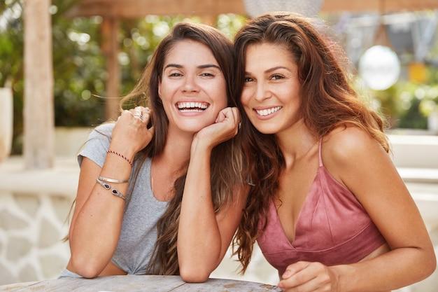 Foto de hembras complacidas con amplias sonrisas, de buen humor para recrear en la cafetería