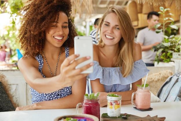 Foto de hembras de raza mixta alegres que tienen amistad interracial, posan en la cámara del teléfono celular moderno, hacen selfie mientras descansan en el acogedor bar de la terraza, disfrutan de bebidas frescas. gente, etnia y ocio
