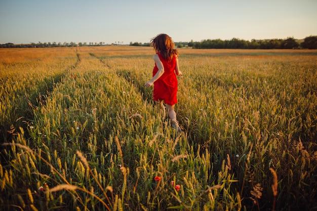 Foto de la hermosa dama en vestido rojo de pie en el campo de oro del verano