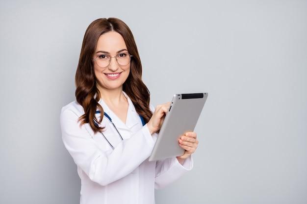 Foto de la hermosa doctora familiar profesional hermosa mantenga tableta de tecnología moderna ebook consulta en línea cuarentena especificaciones de desgaste estetoscopio bata de laboratorio blanca fondo de color gris aislado