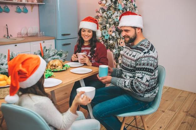 Foto de hermosa familia sentada en tabel y mirar el uno al otro. sostienen tazas en las manos. la gente se sonríe. hay pavo y mandarinas en la mesa.