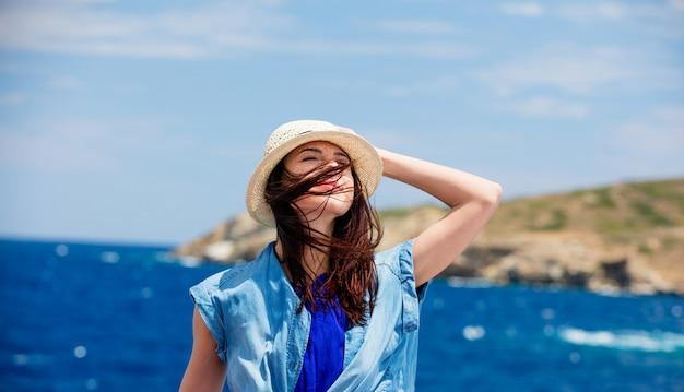 Foto de una hermosa joven en el barco frente al mar y la isla de fondo en grecia