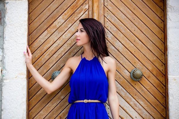 Foto de una hermosa joven de pie cerca de la puerta vieja de madera en grecia