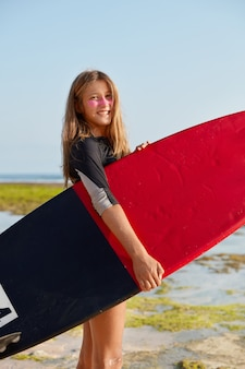 Foto de hermosa joven surfista talentosa ha complacido la expresión facial