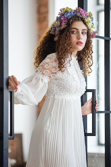 Foto de una hermosa morena con cabello suelto abriendo las puertas del balcón y caminando hacia sunny terrace.