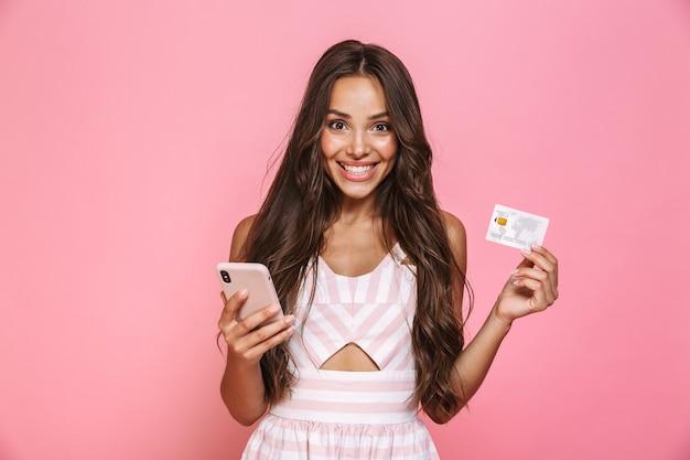 Foto de hermosa mujer de 20 años con vestido sosteniendo teléfono móvil y tarjeta de crédito, aislado sobre pared rosa