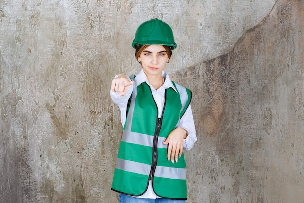 Foto de hermosa mujer arquitecto en casco verde apuntando