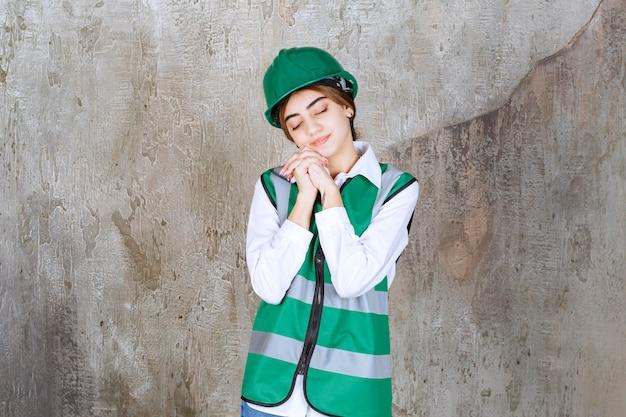 Foto de hermosa mujer arquitecto en casco verde durmiendo