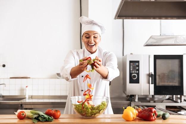 Foto de hermosa mujer chef vistiendo uniforme blanco haciendo ensalada con verduras frescas, en la cocina del restaurante