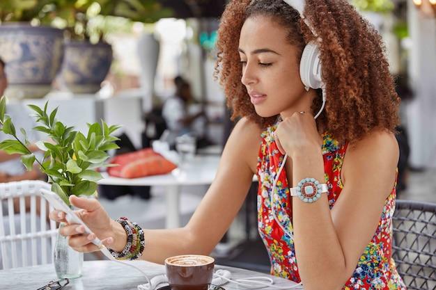 Foto de hermosa mujer concentrada con peinado afro busca su canción favorita en la lista de reproducción, disfruta de música alta en los auriculares mientras se sienta en la cafetería al aire libre