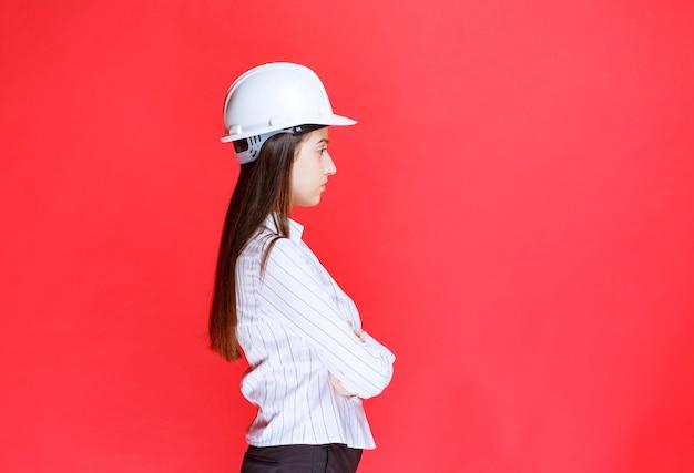 Foto de una hermosa mujer de negocios con sombrero de seguridad de pie con los brazos cruzados.