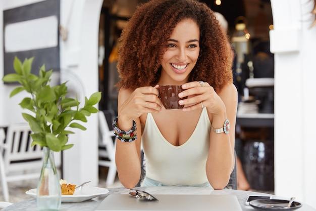 Foto de hermosa mujer sonriente de piel oscura tiene peinado afro rizado bebidas expreso en cafetería tiene expresión positiva.