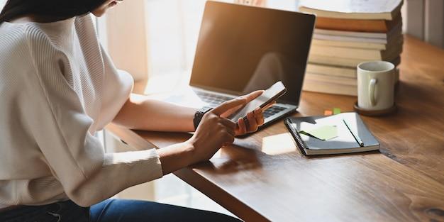 Foto de hermosa mujer sosteniendo un teléfono inteligente en sus manos mientras está sentado en la mesa de madera en la computadora portátil, taza de café, pila de libros y cuaderno en la biblioteca ordenada.