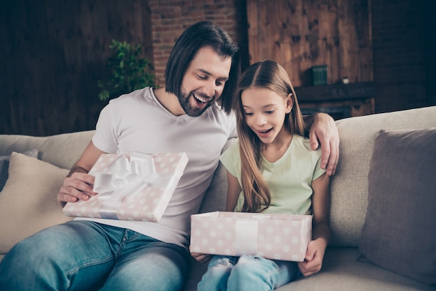 Foto de hermosa niña adorable y apuesto joven papá sentarse en un cómodo sofá