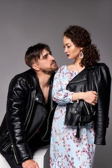 Una foto de la hermosa pareja en chaquetas de cuero. trajes casuales. colección de hombres y mujeres. , pared gris