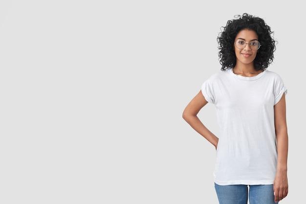 Foto de una hermosa periodista lista para tomar una entrevista, mantiene una mano en la cintura, tiene una expresión de confianza complacida, usa una camiseta blanca de gran tamaño, jeans y gafas, posa sobre una pared en blanco