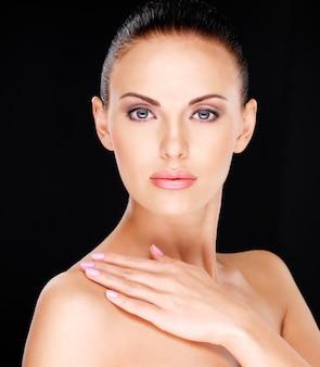Foto de un hermoso rostro de la mujer adulta bonita con piel fresca - sobre fondo negro