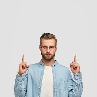 Foto de hipster sin afeitar vestido con camisa casual, apuntando con ambos dedos índices hacia arriba.