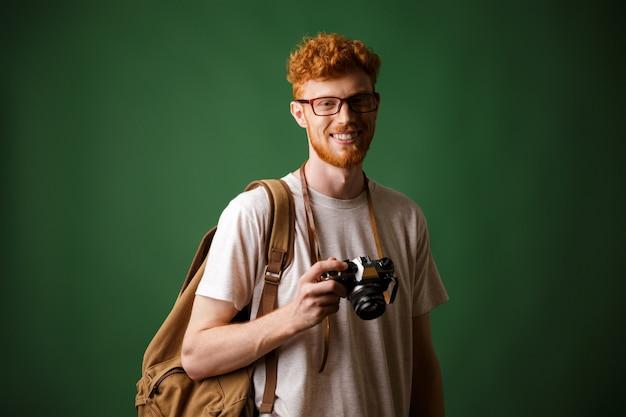 Foto de hipster barbudo de cabeza lectora con cámara retro y mochila