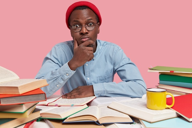 Foto de hipster de moda con sombrero rojo, mantiene la mano en la barbilla, mira sorprendentemente a la cámara, tiene mucho trabajo antes de la sesión, lee libros de texto para educación