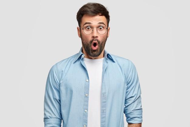 Foto de hombre sin afeitar aterrorizado mira con ojos llenos de incredulidad, siendo sorprendido por una revelación curiosa, viste camisa azul, aislado sobre una pared blanca. personas, reacción, expresiones faciales.