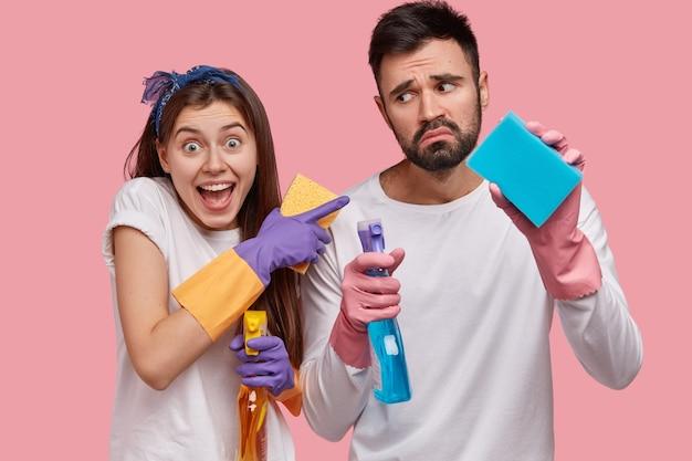 Foto de hombre sin afeitar disgustado sostiene detergente y esponja, mira con insatisfacción