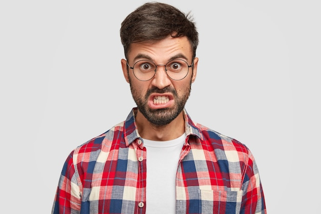 Foto de hombre sin afeitar irritado que se ve enojado, aprieta los dientes y levanta las cejas, está molesto con muchas obligaciones en el trabajo, vestido con camisa a cuadros, se encuentra contra la pared blanca.