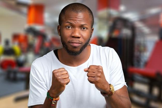 Foto del hombre africano joven enojado emocional que se coloca aislado