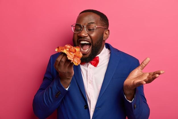 Foto de un hombre afroamericano de piel oscura que abre la boca ampliamente, come deliciosa pizza con apetito, come bocadillos durante la hora del almuerzo, vestido con traje formal