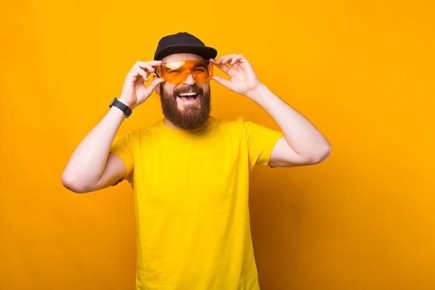 Foto de hombre alegre hipster barbudo en camiseta amarilla con grandes gafas amarillas y sonriendo