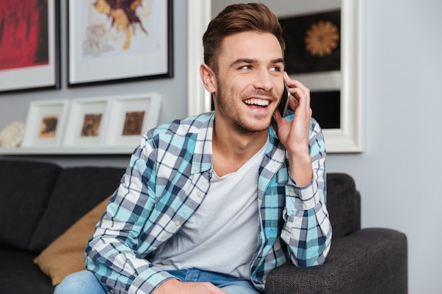 Foto de hombre alegre vestido con camisa en una jaula de impresión sentado en el sofá en casa y hablando por su teléfono.