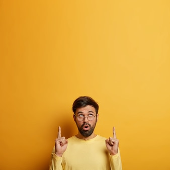 La foto de un hombre asombrado sin afeitar hace un anuncio, señala con el dedo índice hacia arriba, muestra un espacio en blanco, una buena oferta de venta, recomienda un servicio, vestido con ropa informal, posa sobre una pared amarilla