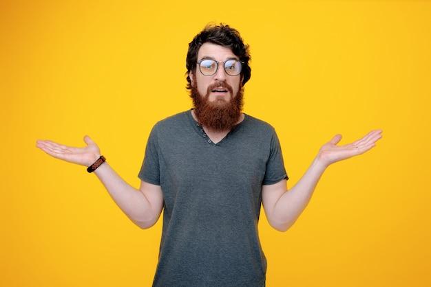 Foto de un hombre con barba en glases, haciendo un gesto desconocido con la mano levantada Foto Premium