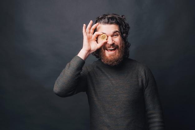 Foto de hombre barbudo alegre sosteniendo bitcoin sobre el ojo y de pie sobre una pared oscura