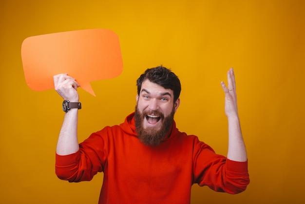 La foto de un hombre barbudo está sosteniendo un globo de diálogo que hace volar su mente en el espacio amarillo.