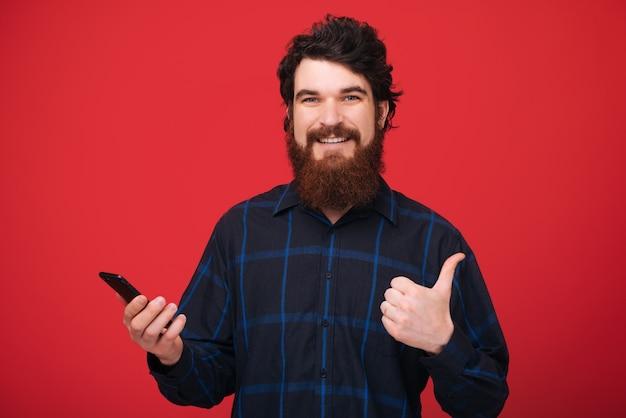 Foto de un hombre barbudo sosteniendo un teléfono inteligente y mostrando el pulgar hacia arriba, pared roja