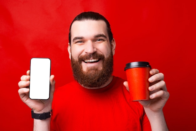 Una foto de un hombre barbudo sosteniendo un teléfono con pantalla en blanco y una taza de bebida caliente cerca de una pared roja