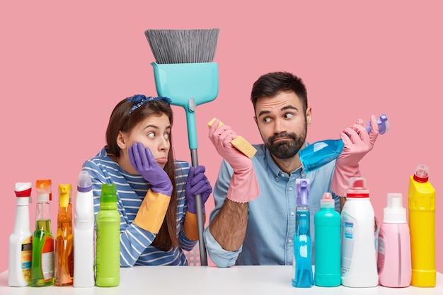 Foto de hombre barbudo vacilante y mujer disgustada que usa guantes protectores, lleva un cepillo, trabajan juntos, hacen las tareas del hogar