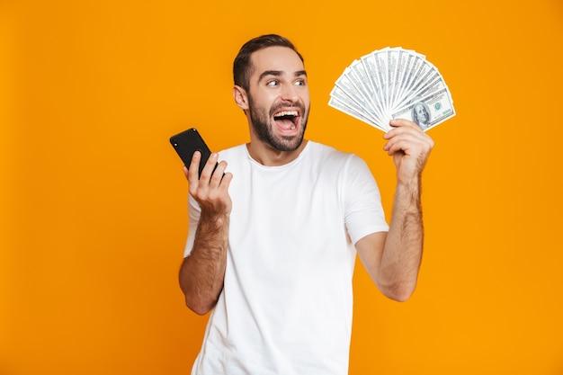 Foto de hombre con bigote de 30 años en ropa casual con teléfono celular y ventilador de dinero, aislado