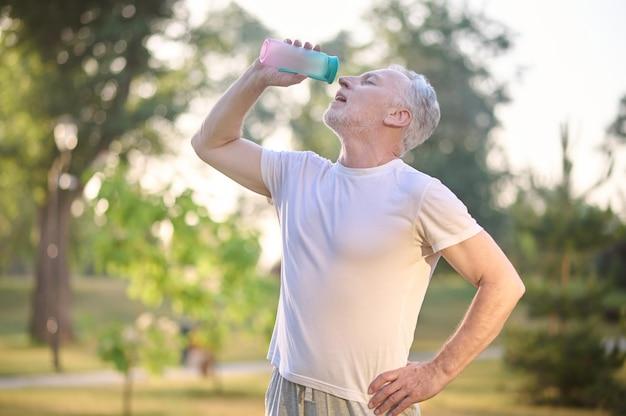 Una foto de un hombre con una botella de agua en las manos.
