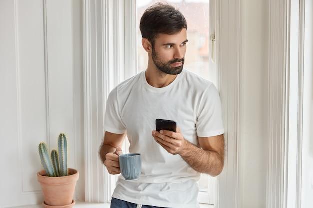 Foto de un hombre caucásico barbudo con camiseta blanca, sostiene un teléfono móvil y una taza de café, instala una nueva aplicación, disfruta de internet gratis, se concentra a un lado, pide comida en un restaurante para cenar, bebe café