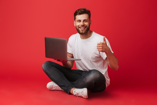 Foto de hombre caucásico barbudo en camiseta y jeans sentado en el piso con las piernas cruzadas y mostrando el pulgar hacia arriba mientras sostiene la computadora portátil, aislado sobre fondo rojo.