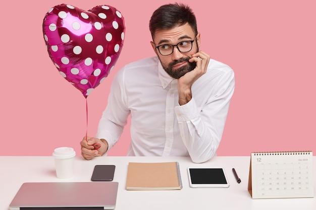 Foto de hombre caucásico barbudo triste con ropa formal, lleva san valentín, se siente solo, no tiene amor, sueña con una nueva relación, se sienta en el escritorio