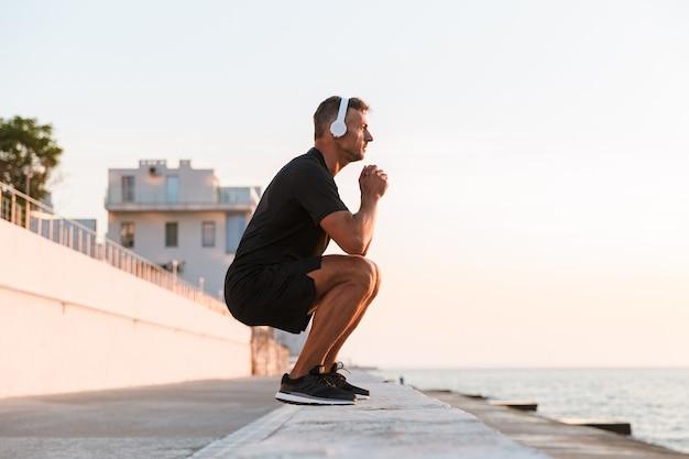 Foto de hombre caucásico sano de 30 años en chándal calentándose y en cuclillas frente a la costa, mientras escucha música a través de auriculares inalámbricos durante el amanecer