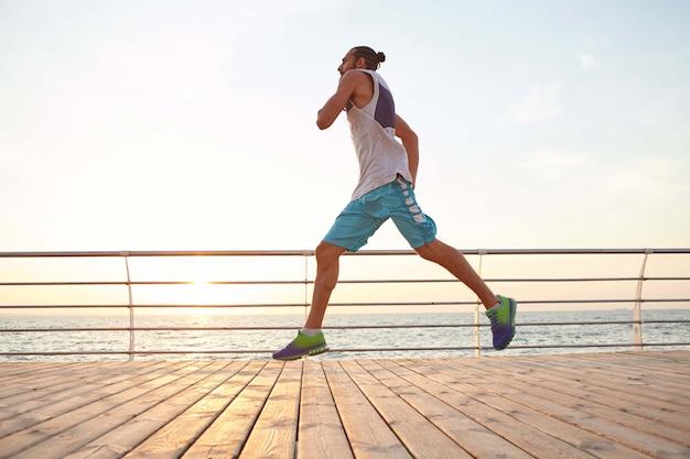 Foto de hombre corriente barbudo deportivo guapo joven, haciendo ejercicios matutinos junto al mar.