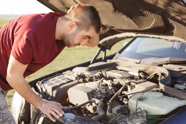 La foto del hombre desesperado se rasca la cabeza con desconcierto mientras se para frente al capó roto del automóvil, no puede eliminar el daño