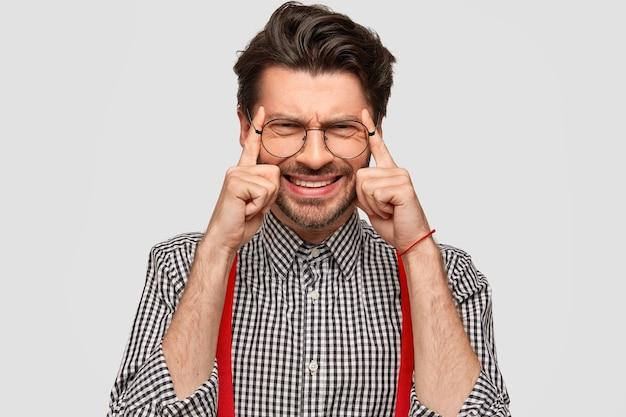 Foto de hombre disgustado con barba incipiente y corte de pelo moderno, mantiene los dedos índice en las sienes, trata de concentrarse en algo, tiene dolor de cabeza, vestido con camisa a cuadros, aislado sobre una pared blanca