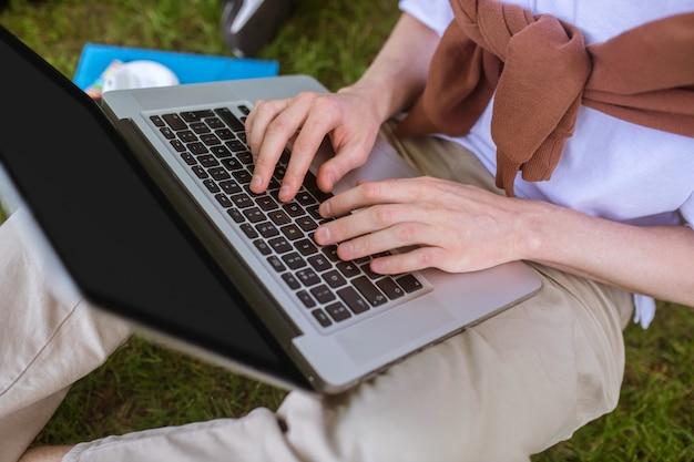 Una foto de un hombre escribiendo en una computadora portátil