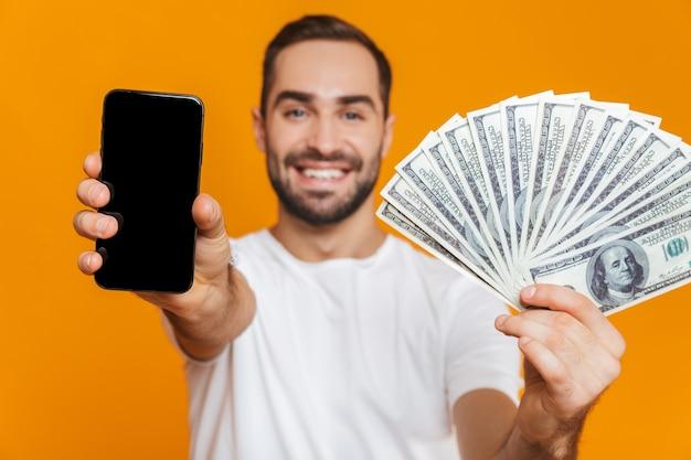 Foto de hombre europeo de 30 años en ropa casual con teléfono celular y ventilador de dinero, aislado